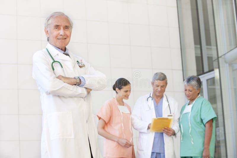 Retrato do doutor sênior com equipe de funcionários fotografia de stock