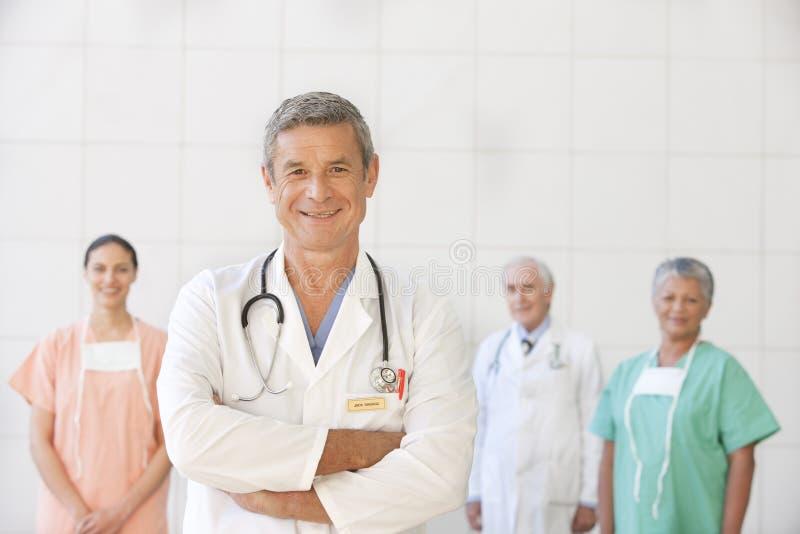 Retrato do doutor sênior com equipe de funcionários foto de stock