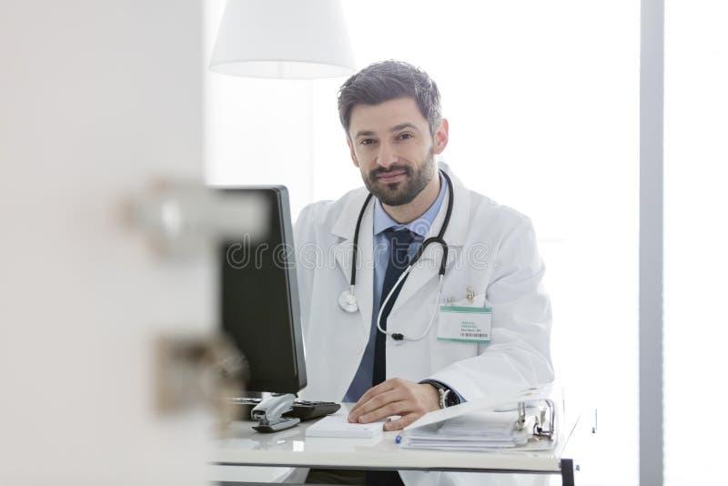 Retrato do doutor seguro que usa o computador na mesa no hospital imagem de stock royalty free
