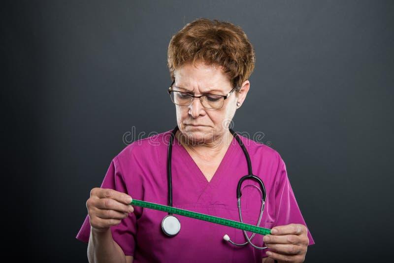 Retrato do doutor superior da senhora que olha a fita de medição foto de stock
