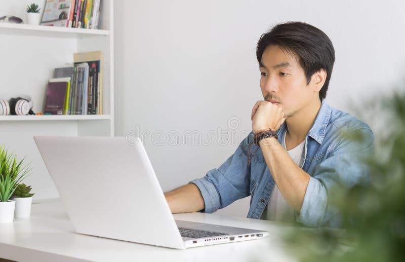 Retrato do empresário casual asiático usa laptop e pensa e ganha espaço imagem de stock
