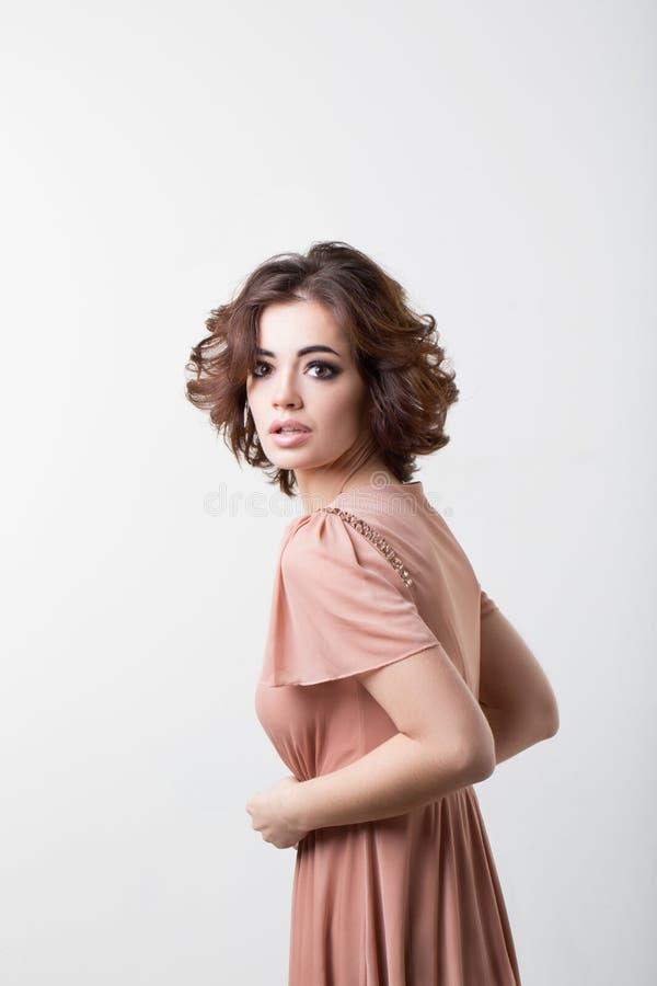 Retrato do encanto de uma jovem mulher em um vestido cor-de-rosa fotos de stock royalty free