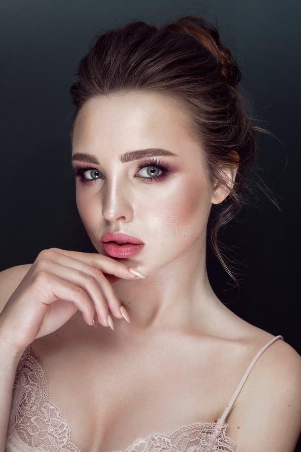 Retrato do encanto do modelo bonito com composição diária fresca e penteado romântico Forme o highlighter brilhante na pele, bord foto de stock