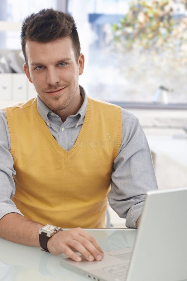 Retrato do escritório do sorriso novo do homem de negócios fotografia de stock royalty free