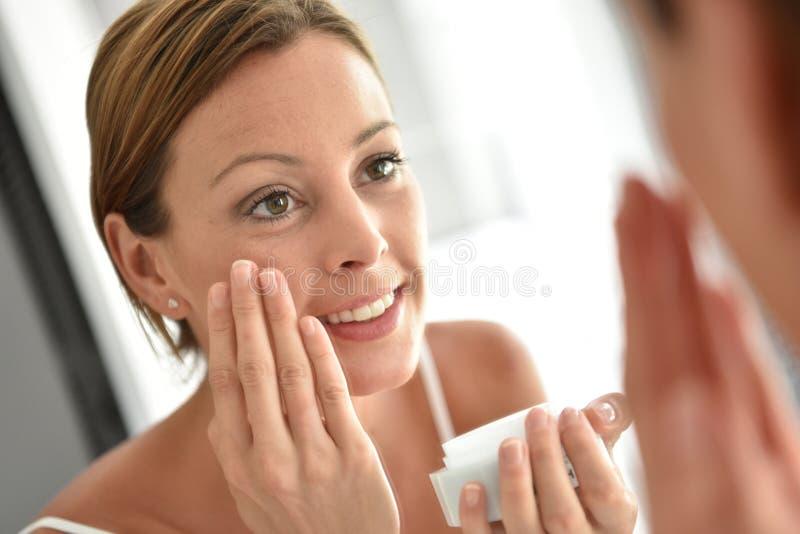 Retrato do espelho da mulher que aplica o creme diário fotos de stock royalty free