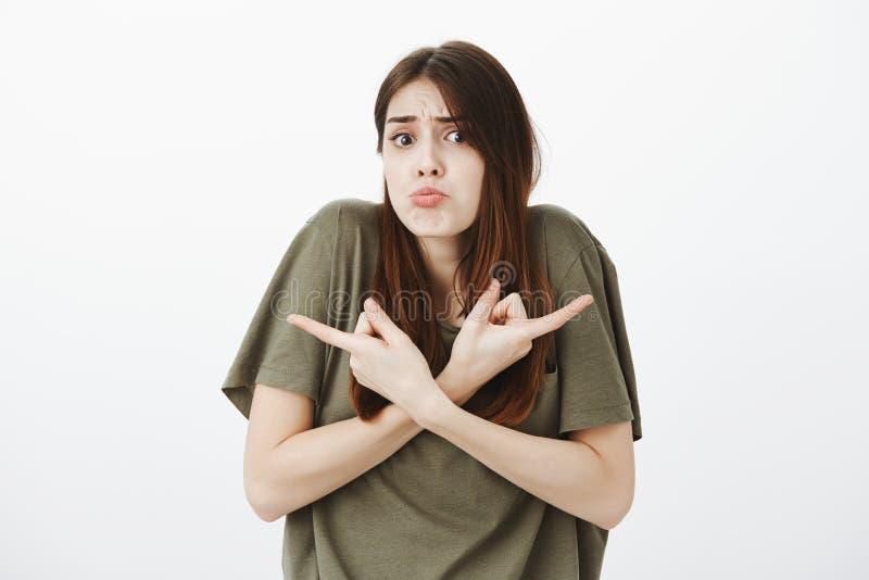 Retrato do estúdio da amiga bonito da virada confusa com cabelo marrom, shrugging, amuando e apontando em diferente foto de stock royalty free