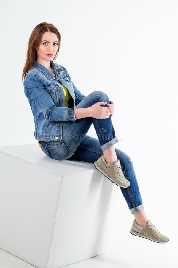 Retrato do estúdio da calças de ganga da mulher e do revestimento vestindo de sorriso novos bonitos da sarja de Nimes fotos de stock royalty free