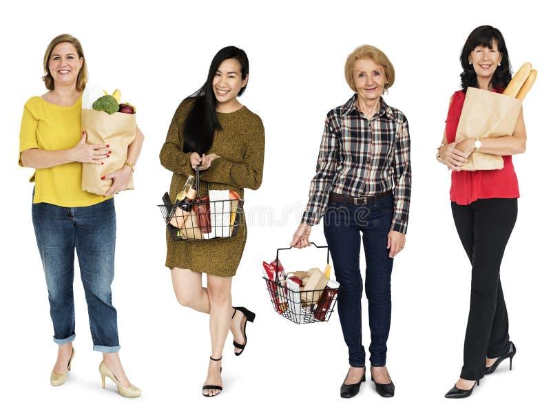 Retrato do estúdio da cesta do alimento da mercearia da compra das mulheres isolado foto de stock