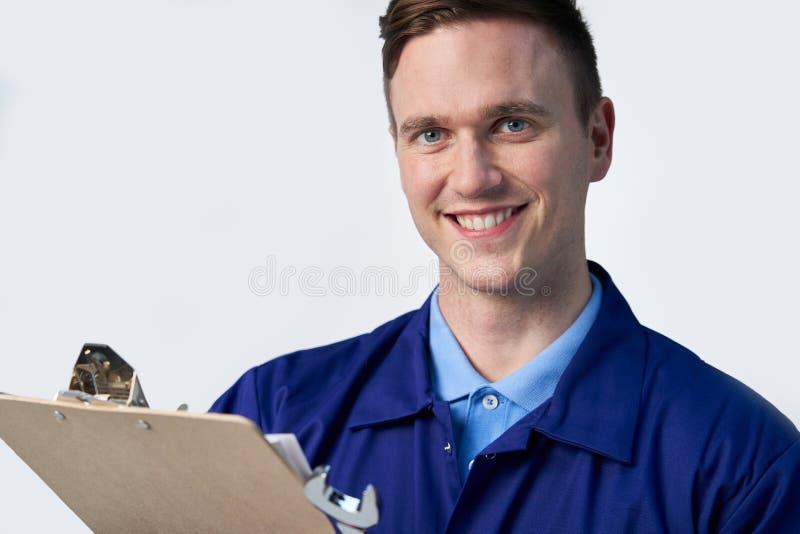 Retrato do estúdio da chave inglesa masculina de With Clipboard And do coordenador contra o fundo branco foto de stock