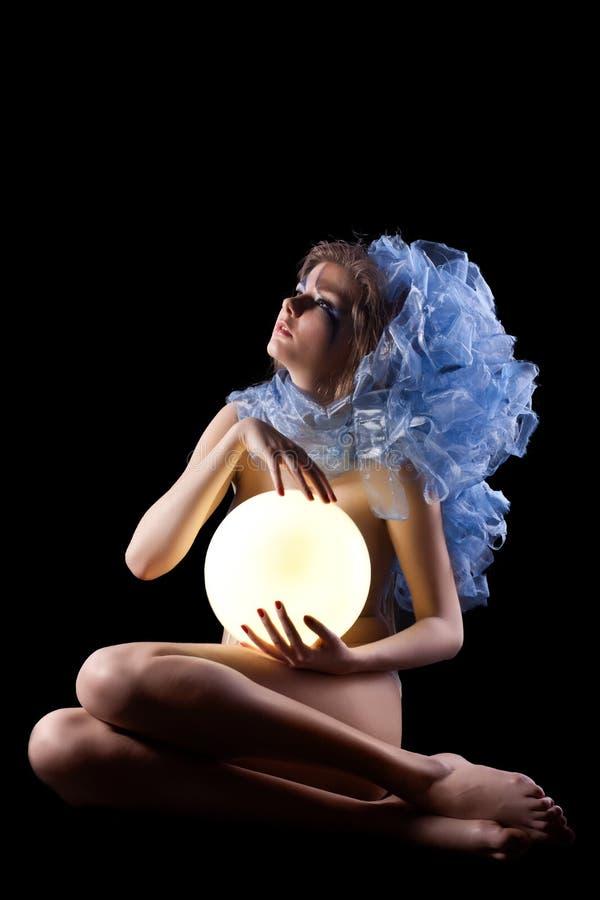 Jovem mulher bonita que guardara a lâmpada leve fotos de stock