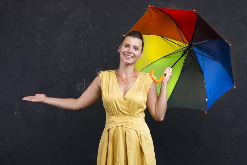 Retrato do estúdio da jovem mulher em um vestido com um guarda-chuva em sua mão Previsão de tempo imagem de stock