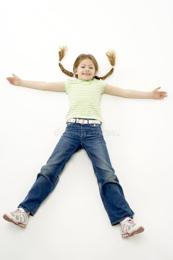 Retrato do estúdio da menina de sorriso que encontra-se para baixo com AR imagem de stock royalty free