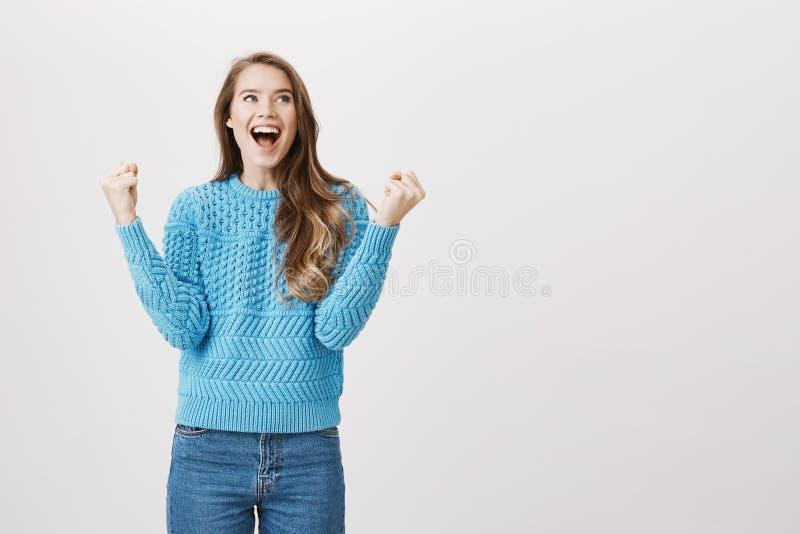 Retrato do estúdio da menina europeia entusiasmado oprimida com as emoções, aumentando os punhos na vitória, gritaria e olhando a imagem de stock