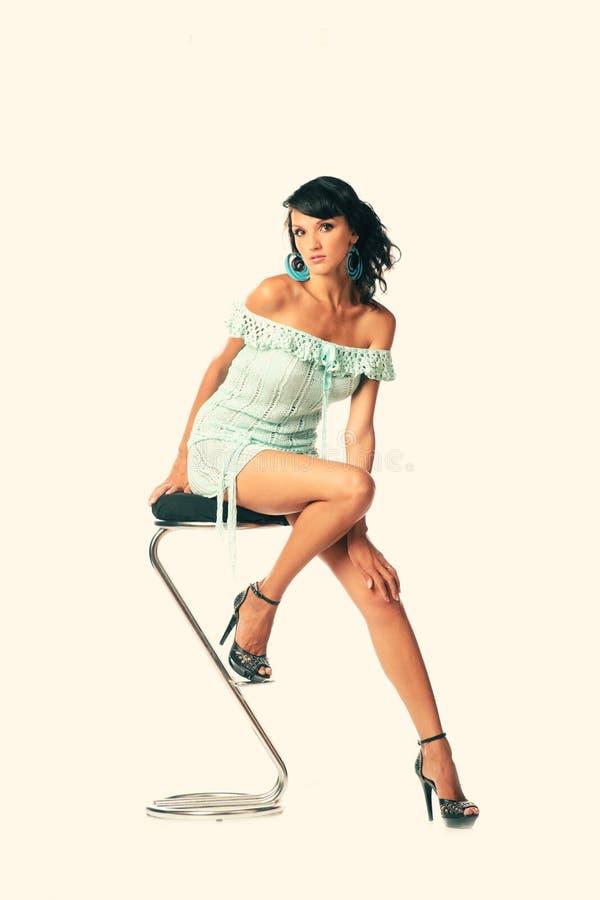 Retrato do estúdio da mulher atrativa de sorriso feliz que senta-se no tamborete e no vestido transparente curto vestindo fotos de stock