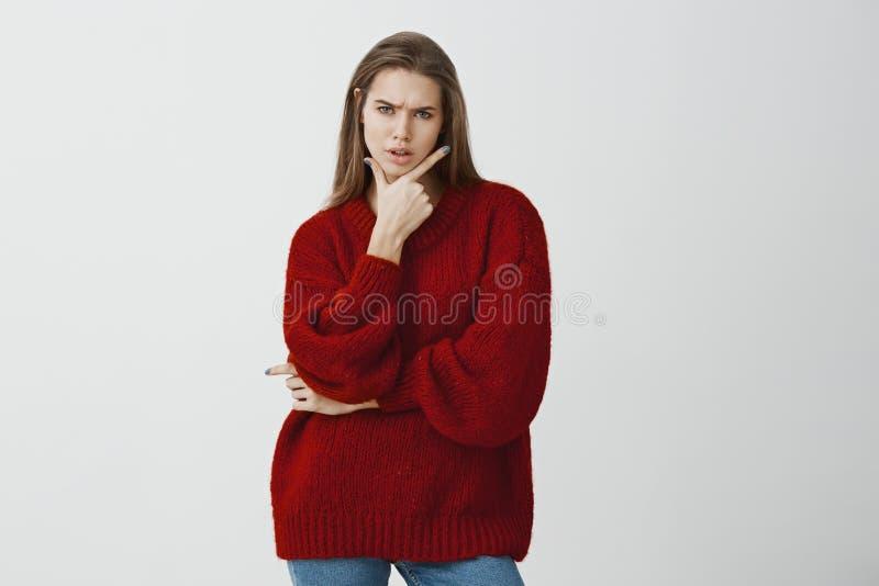 Retrato do estúdio da mulher atrativa duvidosa incomodada na camiseta fraca vermelha à moda, guardando o gesto da arma no queixo  fotografia de stock