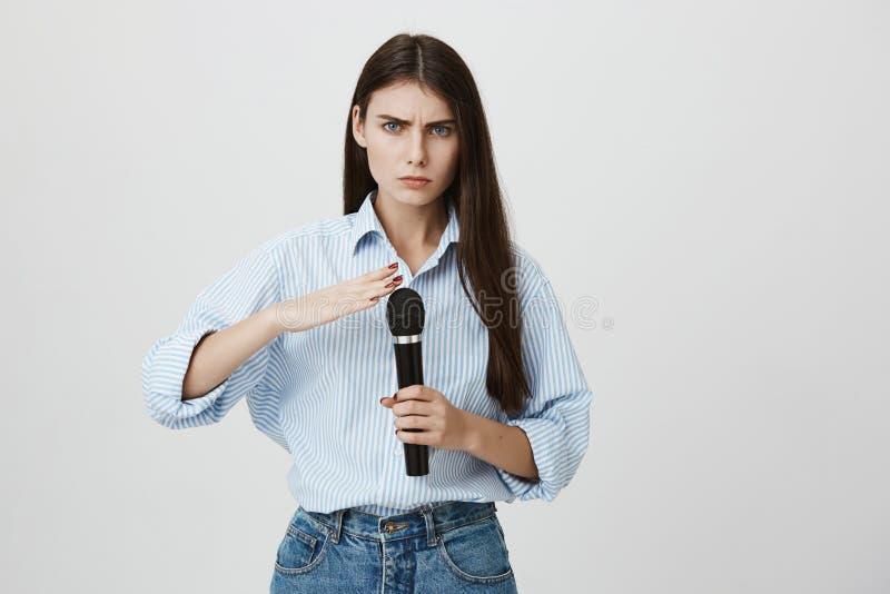 Retrato do estúdio da mulher bonita devista com sobrancelhas olhadas de sobrancelhas franzidas, guardando o microfone ao levantar imagem de stock