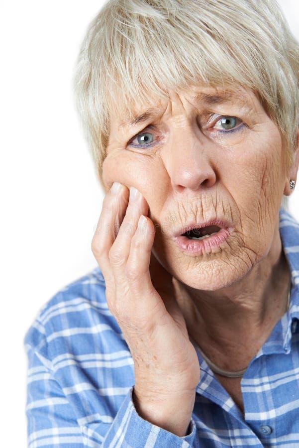 Retrato do estúdio da mulher superior que sofre com dor de dente fotografia de stock