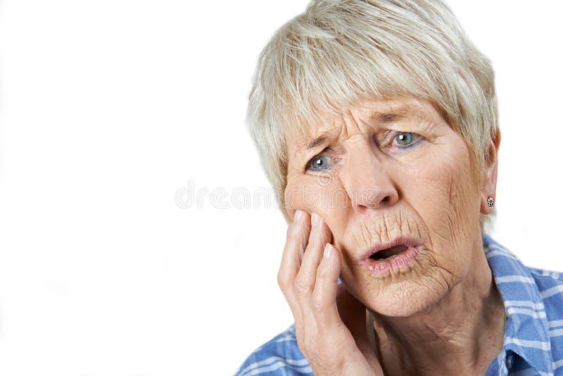 Retrato do estúdio da mulher superior que sofre com dor de dente foto de stock