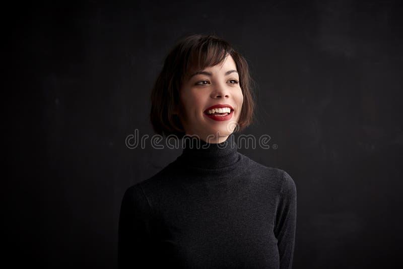Retrato do estúdio da posição alegre da jovem mulher no fundo escuro foto de stock