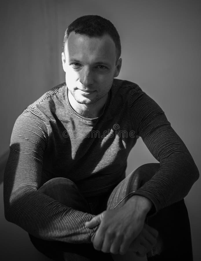 Retrato do estúdio de sentar o homem adulto novo foto de stock royalty free