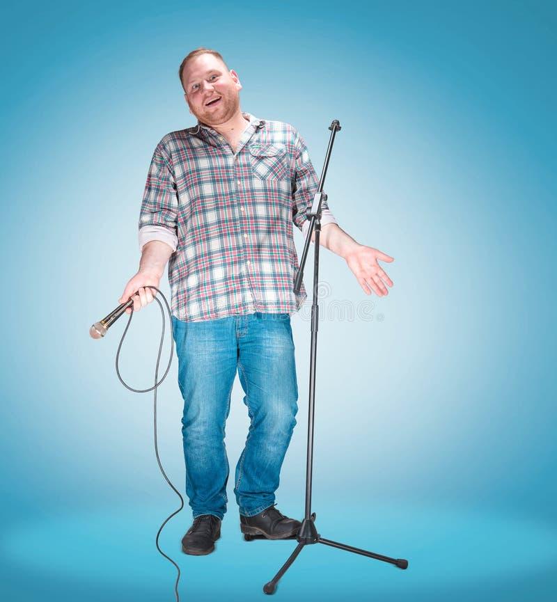 Retrato do estúdio de um empresário novo com o microfone foto de stock