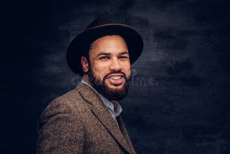 Retrato do estúdio de um homem afro-americano considerável de sorriso em um revestimento e em um chapéu marrons elegantes foto de stock royalty free