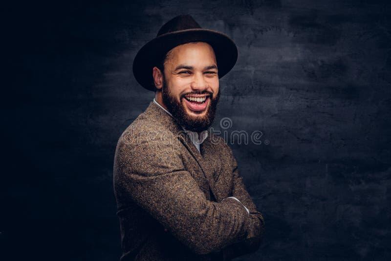 Retrato do estúdio de um homem afro-americano considerável de sorriso em um revestimento e em um chapéu marrons elegantes imagem de stock royalty free