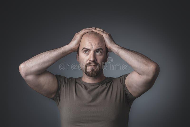 Retrato do estúdio de um homem com mãos em sua cabeça fotografia de stock royalty free