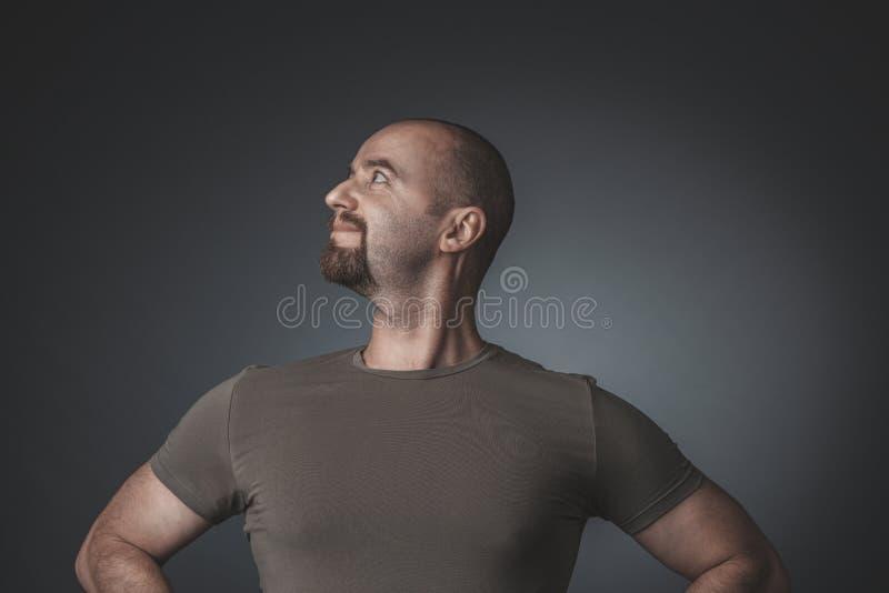 Retrato do estúdio de um homem com uma expressão satisfeita e orgulhosa, vista lateral fotografia de stock