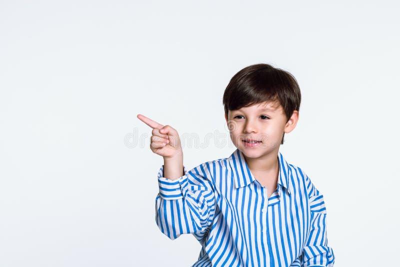 Retrato do estúdio de um menino que aponta em algo com um dedo fotografia de stock royalty free