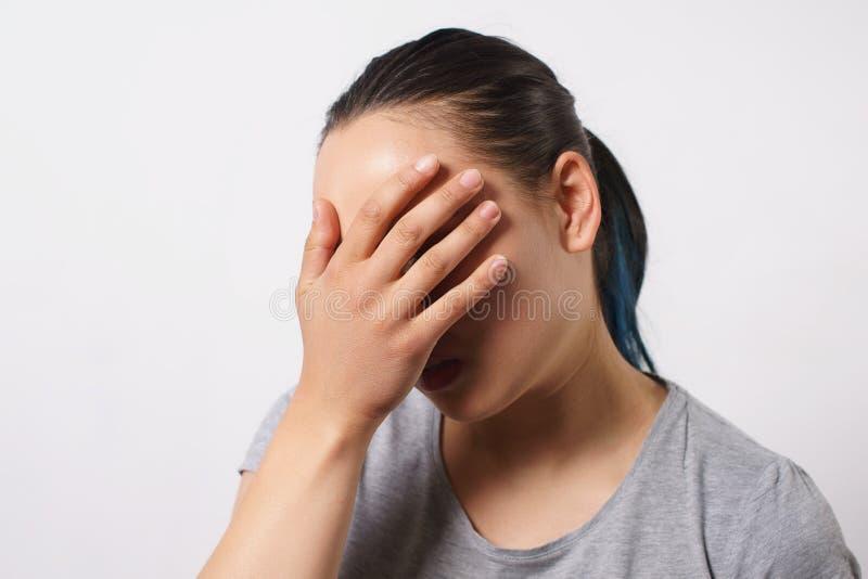 Retrato do estúdio de uma jovem mulher, põe sua mão a sua cara na vergonha e na frustração O conceito da falha e do facepalm imagem de stock royalty free