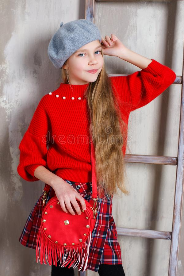 Retrato do estúdio de uma menina em um birette e de uma camiseta vermelha em um fundo cinzento foto de stock