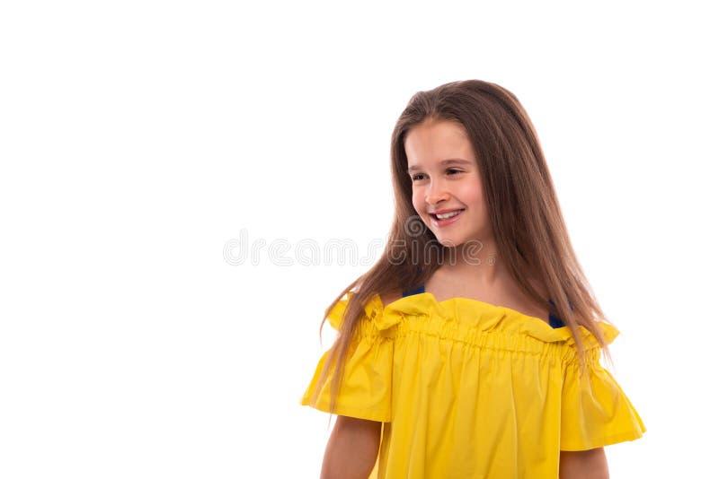 Retrato do estúdio de uma menina de sorriso pequena que veste sundress amarelos em um fundo branco foto de stock royalty free