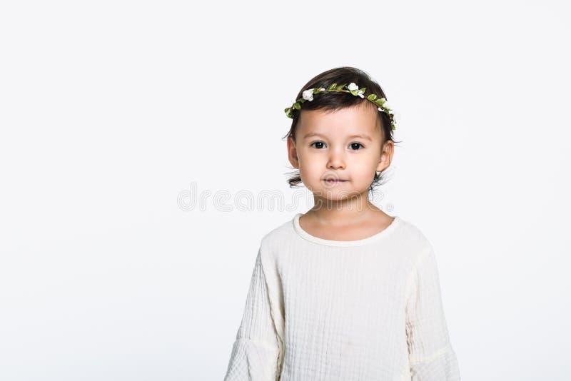 Retrato do estúdio de uma moça que veste uma coroa da flor e que olha a câmera e que sorri com um sorriso feliz foto de stock