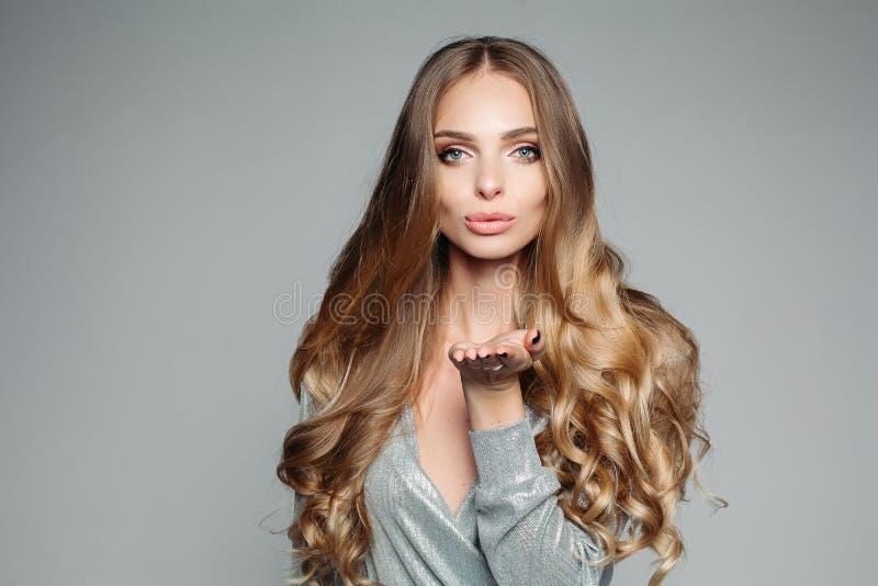 Retrato do estúdio de uma mulher loura atrativa com cabelo grosso longo e a composição profissional que vestem uma prata elegante fotos de stock