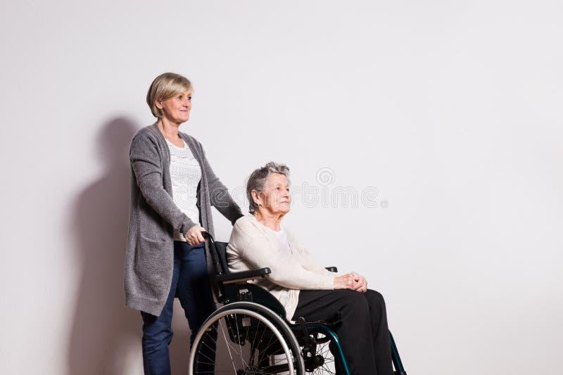 Retrato do estúdio de uma mulher superior na cadeira de rodas com uma equipa de tratamento fotografia de stock royalty free