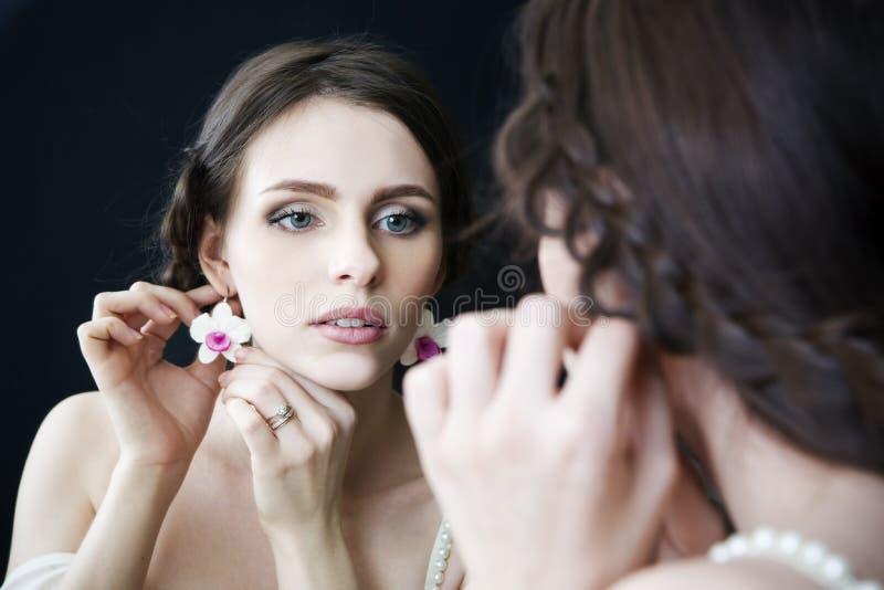 Retrato do estúdio de uma noiva bonita nova que olha no espelho em um vestido branco Composição e penteado profissionais foto de stock