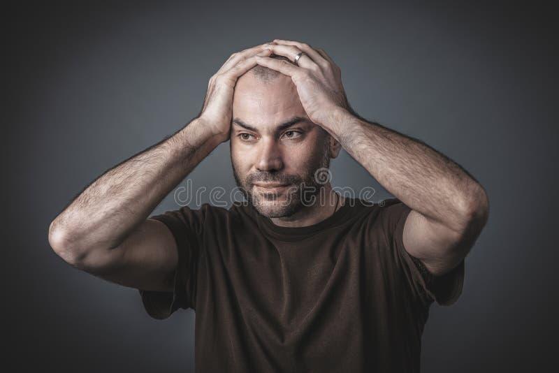 Retrato do est?dio do homem pensativo com suas m?os que guardam sua cabe?a imagens de stock