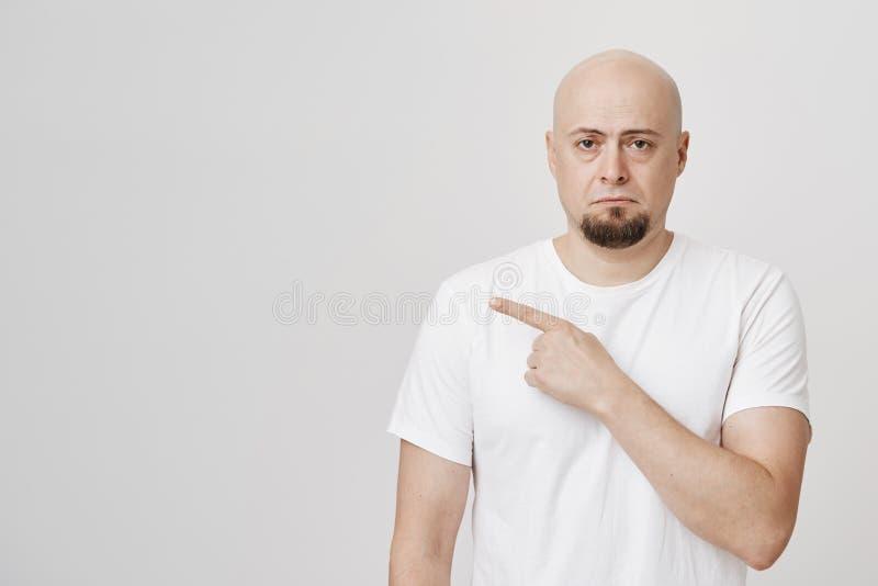 Retrato do estúdio do indivíduo caucasiano calvo infeliz que aponta à esquerda com sorriso sombrio, olhando de sobrancelhas franz foto de stock
