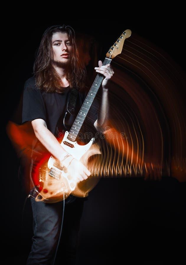Retrato do estúdio: músico de cabelos compridos novo considerável da rocha do homem que joga a guitarra elétrica Efeito obscuro d fotos de stock