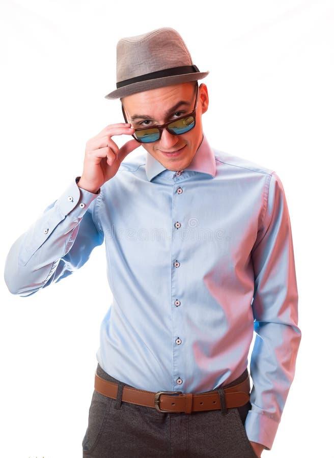 Retrato do estilo da forma do homem considerável novo no levantamento agradável na camisa e nos óculos de sol azuis à moda, com c imagem de stock royalty free