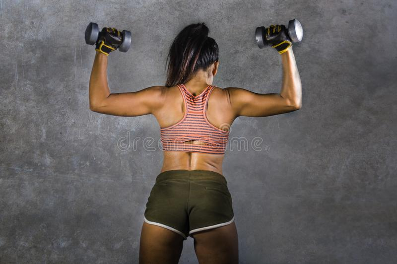 Retrato do estilo da propaganda do esporte do Grunge da mulher atlética nova com o corpo traseiro e apto forte que guarda pesos n fotografia de stock royalty free
