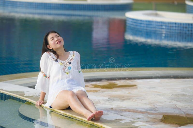 Retrato do estilo de vida do ar livre da mulher chinesa asiática feliz e bonita nova do turista que relaxa na piscina tropical do foto de stock