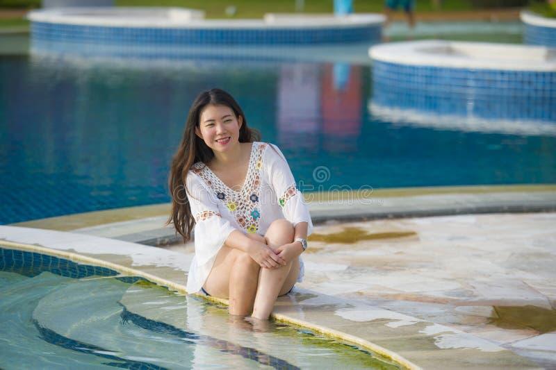 Retrato do estilo de vida do ar livre da mulher coreana asiática feliz e bonita nova do turista que relaxa na piscina tropical do imagem de stock