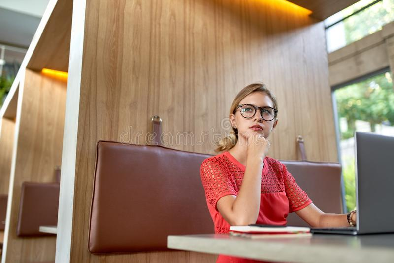 Retrato do estilo de vida do close up dos vidros vestindo do blogger milenar caucasiano louro pensativo novo que tomam notas em u foto de stock royalty free