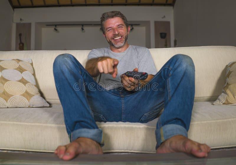 Retrato do estilo de vida da casa da mostra nova da televisão do homem feliz e atrativo ou do riso cômico de observação do filme  imagem de stock