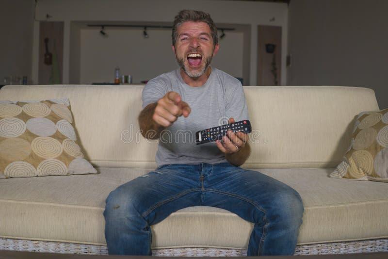 Retrato do estilo de vida da casa da mostra nova da televisão do homem feliz e atrativo ou do riso cômico de observação do filme  foto de stock royalty free