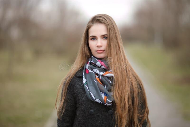 Retrato do estilo de vida da mulher adulta nova e bonita com o cabelo longo lindo que levanta no parque da cidade com profundidad fotos de stock