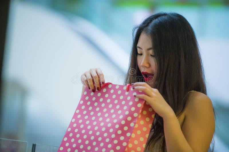 Retrato do estilo de vida da mulher chinesa asiática feliz e entusiasmado nova que olha entusiasmado na compra do saco de compras imagem de stock royalty free