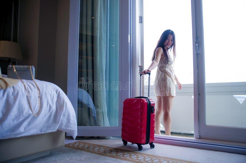 Retrato do estilo de vida da mulher coreana asiática feliz e bonita nova do turista com a mala de viagem que chega à sala de hote fotos de stock royalty free